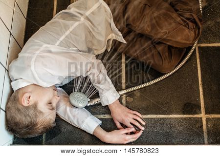 Overhead View Of Boy Passed Out In Bathroom