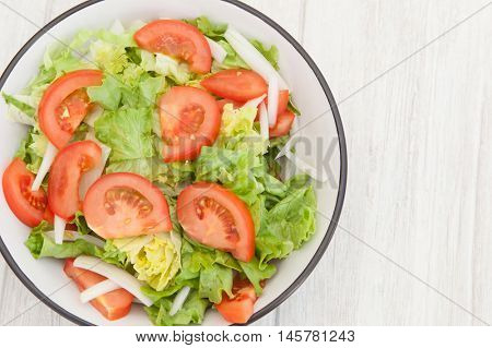 Salad bowl with lettuce tomato and onion on a white wooden background