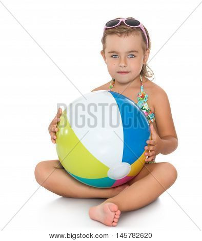 Beautiful little girl in sunglasses and bathing suit. Girl holding in hands in front of a large striped ball. Girl sitting on the floor