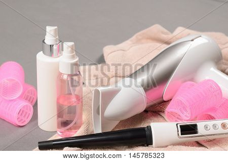 Hair Styling Tools (white Hairdryer, Hairspray, Curler, Spray, Cone Curling Wand) On Beige Towel