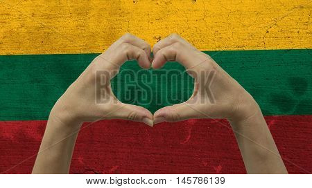 With a stylized Lithuanian flag background an anonymous person's hands being held in the form of a heart symbolizing love and patriotism for Lithuania.