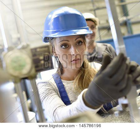 Young woman apprentice in metalworkshop