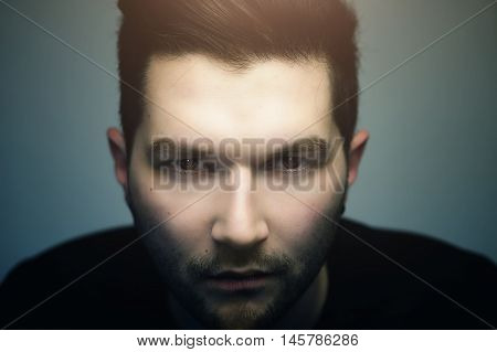 Serious hipster handsome man with evil eyes looking at you close up studio portrait.