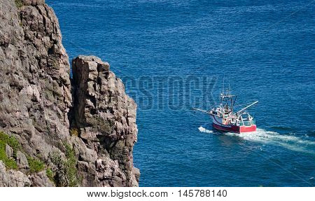 Bright red fishing boat heads out to sea on sunny summer day from St. John's harbor Newfoundland, Canada.
