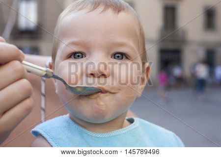 Mother feeding her baby boy with fruit mush outdoors