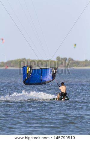 Tampa Bay Florida USA - February 28 2011: Stiff breeze helps kiteboarder slash across Tampa Bay