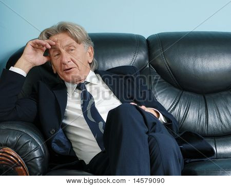 Director thinking on leather sofa