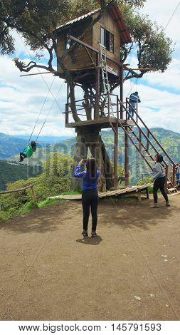 Banos de Agua Santa, Tungurahua / Ecuador - September 2 2016: Tourists playing on the swing of the treehouse near of the city. Banos is located on the northern foothills of the Tungurahua volcano