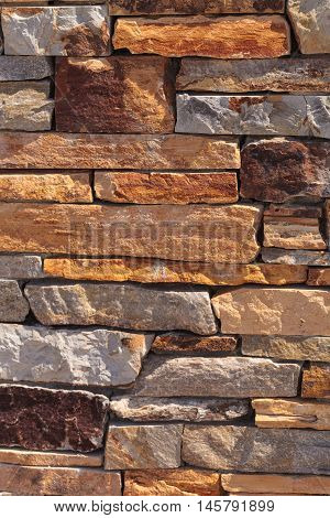 Cut tan and grey stone wall background texture