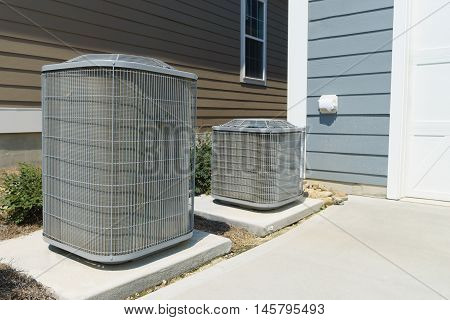 Two air conditioner compressor units attached to the residential house