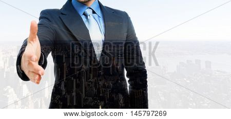 Double exposure of a businessman offering an handshake in front of a big city