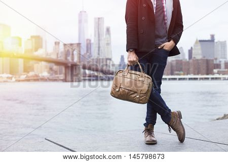 Closeup of a young entrepreneur wearing boots and a briefcase in New York