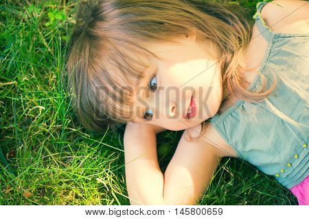 Cute Smiling little girl lying on green grass. Cute three years old child enjoying nature outdoors. Healthy carefree kid playing outside in summer park
