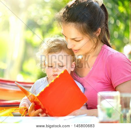 Happy mother reading a book to her little baby in sunny park. Joyful young family with child. Mom and kid having fun outdoors in orchard garden, playing together. Laughing and hugging, enjoying nature
