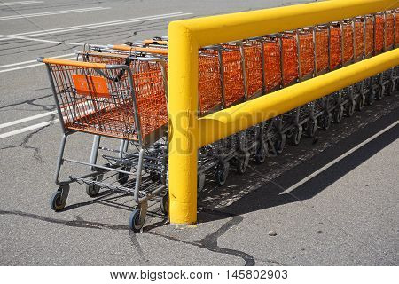 stacking shopping carts in parking lot outside store