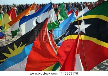 International flags of nations of the world sway colorfully in wind while crowd gathers in background symbolizing unity.