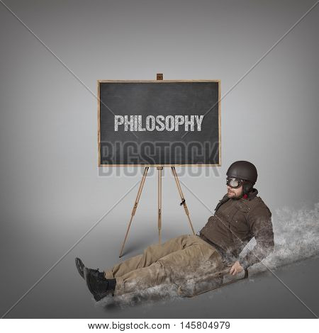 Philosophy text on blackboard with businessman sliding with a sledge