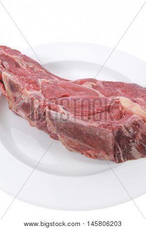 fresh raw red ribeye beef steak on bone over big white plate isolated on white background rib eye
