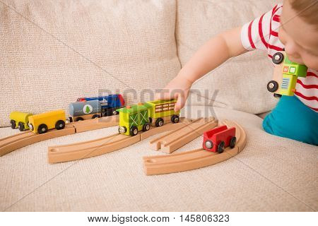Closeup of child's hands playing with wooden train toys and railway. Toddler boy sitting and playing with railroad indoors. Developing activities for toddlers in daycare and nursery.