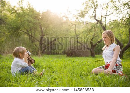 Adorable little kid boy sitting on the grass and taking picture of his young mother with the retro photo camera. Mother and son having photo session in the summer park. Outdoors.