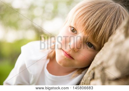 Portrait of adorable blond kid boy looking into the distance and thinking. Serious child dreaming while sitting outdoors.