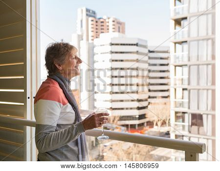 Happy older woman looking at view from highrise apartment holding glass of wine