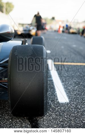 Black slick motor sport tire close up car on starting grid with out of focus background