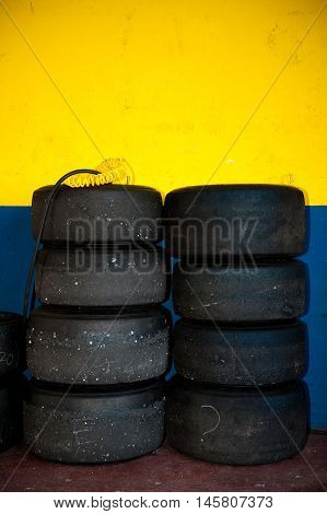 Tire set inside motor sport circuit pit yellow and blue wall