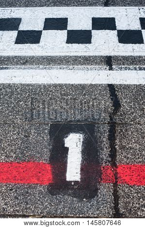 Number one pole position sign on speedway starting track with red line and damaged old asphalt