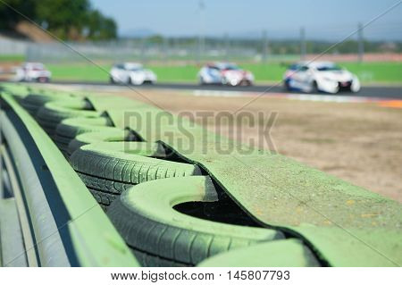 Green tire barrier close up off the track on motor sport circuit with racing cars out of focus in background