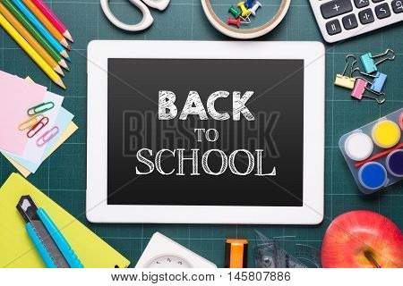 Composite image of digital tablet on desk with back to school message
