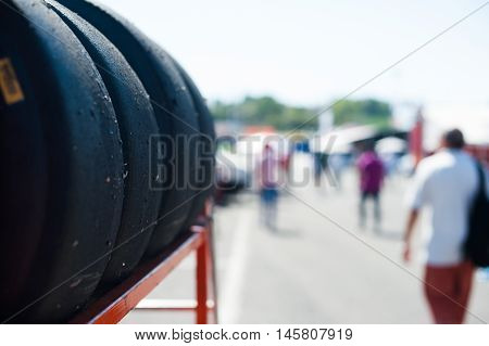 Black slick motor sport tire on trolley close up on pit lane with out of focus background