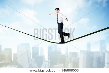 City scape, tall buildings and clouds on clear blue sky with business person balancing on black rope concept