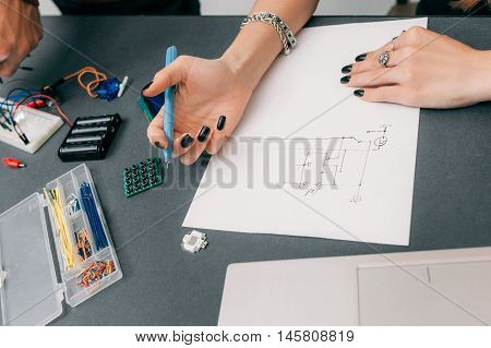 Female engineer drawing scheme of electronic construction. Woman hands designing engineering construction on paper, electrical components on table