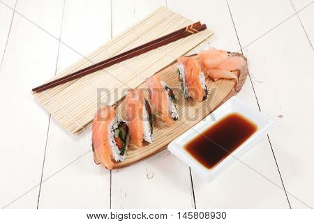 onigiri sushi salmon rolls with soy sauce on wooden plate and bamboo mat on white table with sticks
