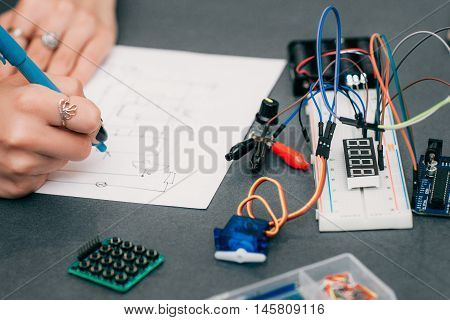 Wiring diagram drawing with breadboard. Electronic construction developing. Female engineer in laboratory, smart woman, hobby and electronics concept