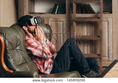 Excited man watching video in vr glasses. Young bearded male watching emotional movie in virtual reality headset, feeling shocked and thrilled. Cinema at home, innovation, entertainment concept