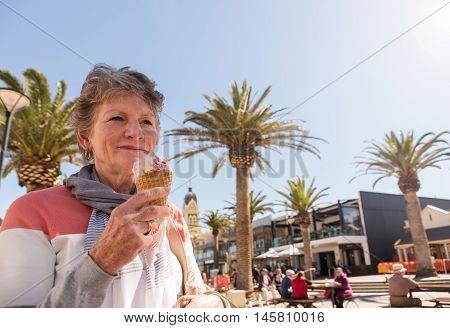 Happy smiling lady eating ice-cream at beachside Glenelg