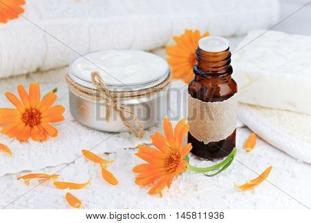 Herbal calendula oil, fresh holistic marigold flowers, jar of handcrafted cosmetic cream.  White towel, salt, soap. Cleansing moisturizing facial product.