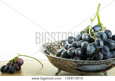 Antique Fruit Bowl With Cluster Of Grapes, On Wooden Surface With White Background.