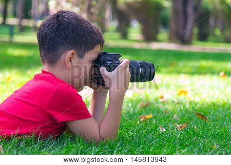A caucasian boy is interested in the art of photography. A boy in a red t-shirt lies on grass outdoors holding a digital camera trying to focus on a distant object. Sunny September morning in a park.