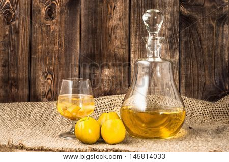Glass of drink and carafe of alcohol tincture with quince fruits.