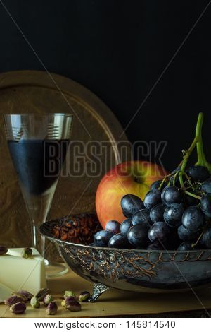 Antique Fruit Bowl With Cluster Of Grapes, Apple With Pieces Vegan Cheese, Pistachios And A Glass Of