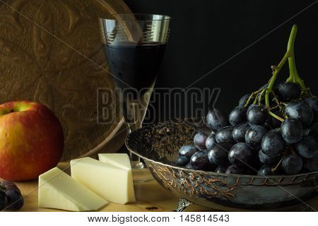 Antique Fruit Bowl With Cluster Of Grapes, Apple With Pieces Vegan Cheese And A Glass Of Red Wine.