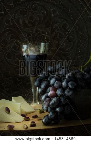 Antique Fruit Bowl With Cluster Of Grapes, With Pieces Vegan Cheese, Pistachios And A Glass Of Red W