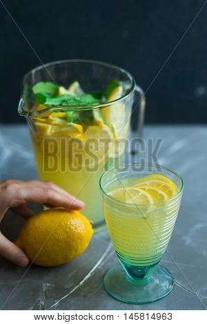 Lemonade drink. Lemonade in the jug and glass with lemons and mint