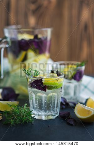 Lemonade drink. Lemonade in the glass with lemons, lime, red basil and rosemary