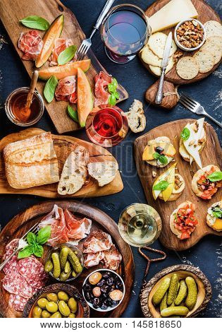 Italian antipasti wine snacks set. Brushettas, cheese variety, Mediterrnean olives, pickles, Prosciutto di Parma with melon, salami and wine in glasses over black grunge background. Top view