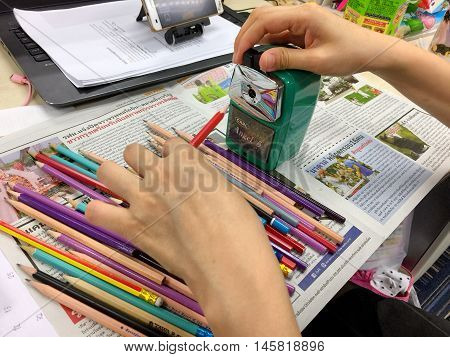 BANGKOK THAILAND 6 SEP 2016 : Closeup of woman's hands using green pencil sharpener a lot of pencils on the table