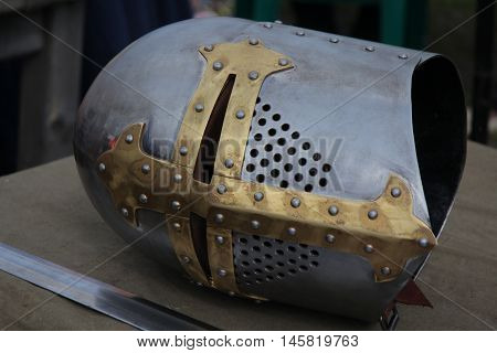 Part of a knight's medieval suit of armor. Helmet and sword beside him